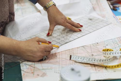 Cropped image of fashion designer marking on fabric at workshop