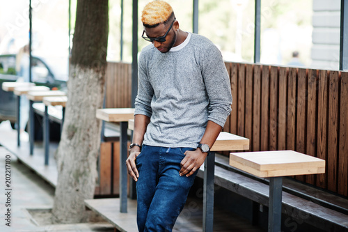 9a67fe10eed Stylish african american boy on gray sweater and black sunglasses posed at  street. Fashionable black