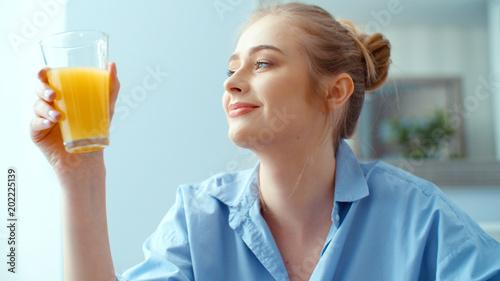 Fototapeta Portrait of happy young woman drinking orange juice during breakfast. obraz na płótnie