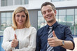 Two happy male and female business people showing thumbs up outdoors. Man and woman looking at camera and standing with building in background. Business success concept. Front view.