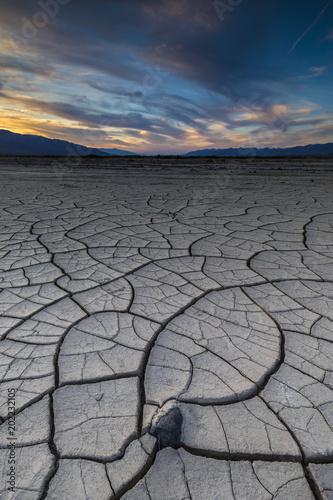 Zdjęcie XXL Skała wystające z niektórych dużych pęknięć błoto na pustyni z zachodem słońca w tle