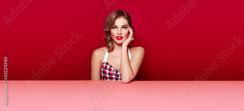 Photographie  Beautiful young girl in bright clothes and with bright make-up sits in the studio behind a pink table on a red background