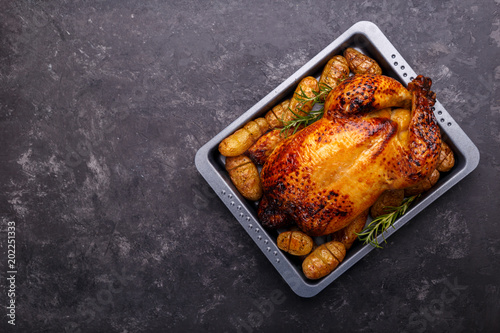 Fotobehang Kip Roasted chicken and potatoes on black slate stone background, flat lay with copy space. Menu or recipe template