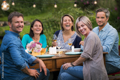 A summer evening of friends in their 40s gather around a table in the garden to share a meal and have fun together Poster Mural XXL