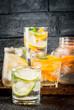 Summer healthy cocktails, set of various citrus infused waters, lemonades or mojitos, with lime lemon orange grapefruit, diet detox beverages, in different glasses dark background copy space