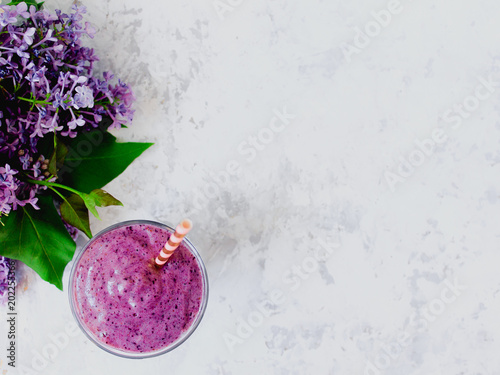 Obraz Still life of purple blueberry smoothie with stripped straw and a branch of lilac in glass on white textured background. Healthy vegan lifestyle concept. - fototapety do salonu