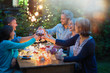 canvas print picture One summer evening, friends in their forties gathered around a table in the garden lit by luminous garlands. They toast with their glasses of wine