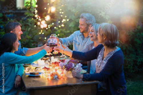 Fotografie, Obraz  One summer evening, friends in their forties gathered around a table in the garden lit by luminous garlands