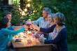 canvas print picture - One summer evening, friends in their forties gathered around a table in the garden lit by luminous garlands. They toast with their glasses of wine