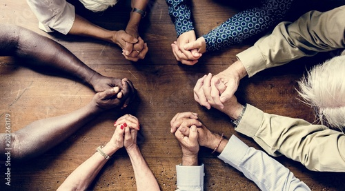 Valokuva Group of interlocked fingers praying together