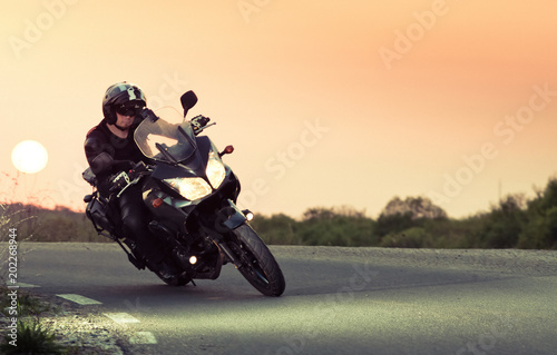 silhouette of rider on a motorbike driving at sunset - space for your text Wallpaper Mural