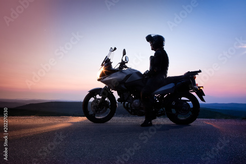 Poster Motorcycle man on his motorbike admiring sunset - summer road trip - space for text
