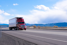 Big Rig Red Semi Truck With Refrigerated Semi Trailer Transporting Commercial Cargo On Flat Road In Utah