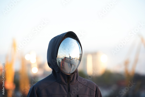 Photo Faceless character with the mirror mask with port in background.