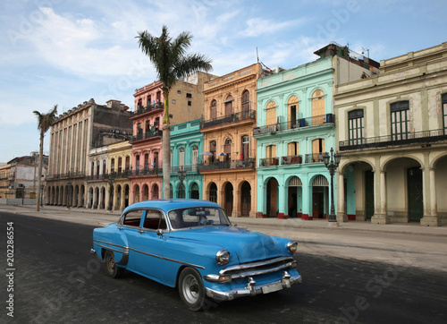 Poster Havana Colorful buildings and historic colonial archtiecture with a generic Classic car (logos & hood or bonnet ornament removed) on Paseo del Prado, downtown Havana, Cuba.