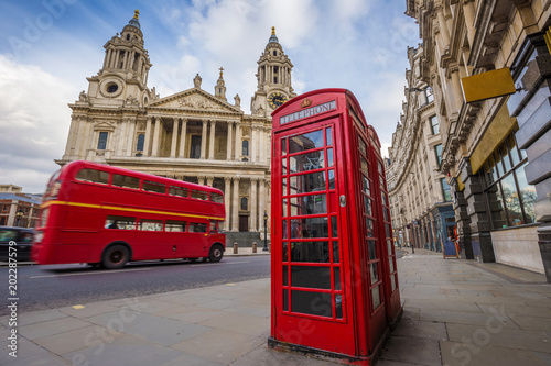 London, England - Traditional red telephone box with iconic red vintage double-decker bus on the move at St Canvas Print