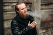 A bearded man in a black leather jacket stands outside and poses for a photographer. Smokes sigaret