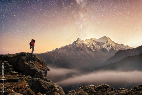 Poster Beige Photographer traveler who take a picture of starry sky and sunrise in mountains