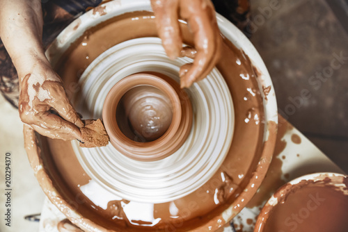 Photo  A spinning potter's wheel with a vessel. Close-up.