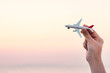 Woman hand holding airplane model in sunset sky and summer sea background dreams of journey in vacation.