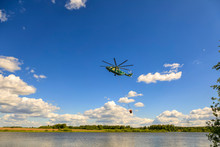 Helicopter Extinguishes A Fire Hangs Over A Large Pond Gaining Water