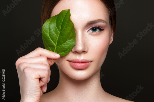 Beautiful woman portrait on black background with clean skin and green leaf in hand.