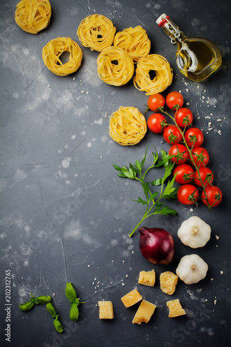 Fototapety, obrazy: Ingredients for traditional Italian pasta dish.Raw spaghetti, parmesan cheese, olive oil, garlic, basil leaves, pepper, cherry tomatoes on old dark stone background.   Top view.