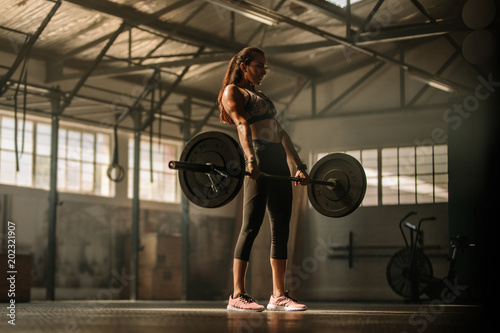 Stickers pour portes Fitness Cross fit woman lifting heavy weights in gym