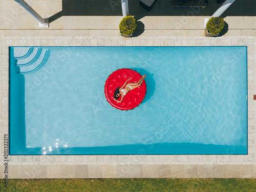 Obraz Woman floating on inflatable mattress in pool - fototapety do salonu