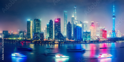 Foto op Aluminium Aziatische Plekken Aerial panoramic view over a big modern city by night. City illuminations of Shanghai, China. Colourful skyline with skyscrapers and river Huanpu.