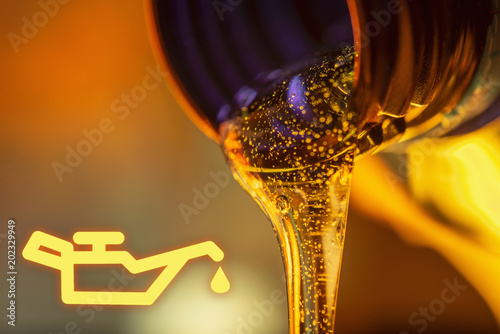 Fototapeta Low oil pressure lamp and liquid stream of motorcycle motor oil flows from the neck of the bottle close-up. obraz