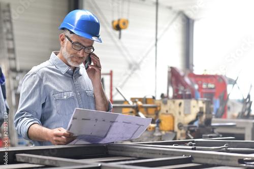 Metallurgy engineer talking on phone in factory Canvas-taulu