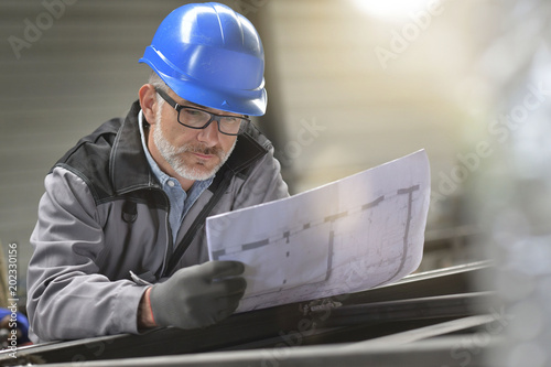 Metalworker in factory reading instructions on blueprint Canvas-taulu