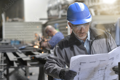 Photo  Metalworker in factory reading instructions on blueprint