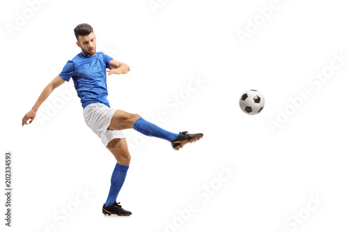 Soccer player kicking a football