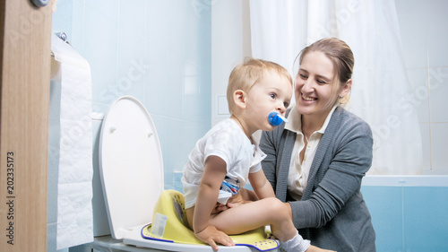 Photo Portrait of smiling young mother teaching her toddler son using toilet