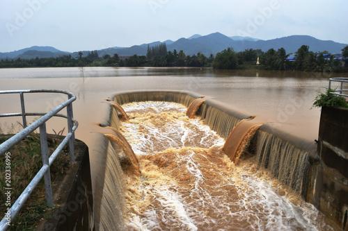 Billede på lærred Turbid water in the dam overflows into the spillway  , Thailand