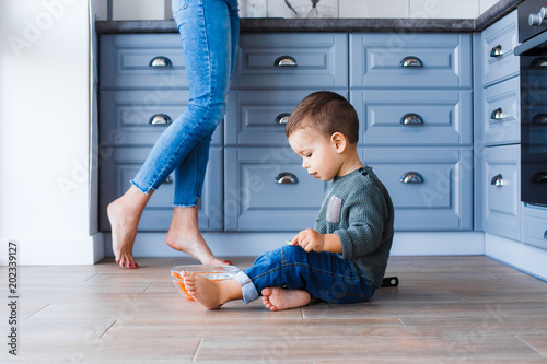 Fotografía  A cute little boy is sitting on the kitchen floor with his mother in the backgro