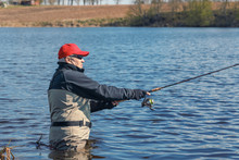 Fishermen Spin Fishing Using Chest Waders To Stay Dry.