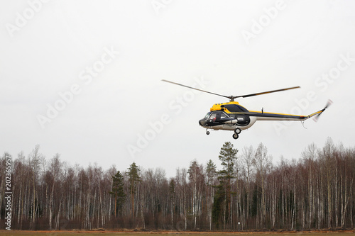 Keuken foto achterwand Helicopter Aircraft - Black-yellow helicopter makes flight low height side view