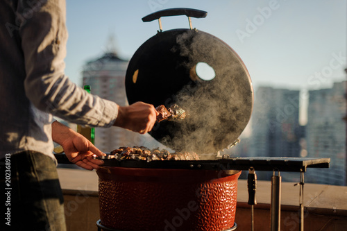 Photo Man roasting a large meat pieces on the skewer in the grill on the blurred backr