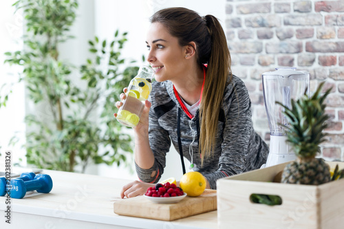 Fotomural Sporty young woman looking sideways while drinking lemon juice in the kitchen at home