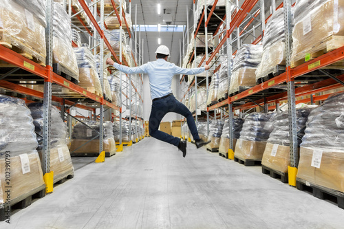 Fototapeta logistic business, success and people concept - happy businessman in helmet jumping at warehouse obraz
