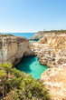 View of grotto cave, turquoise lagoon, limestone cliffs and lighthouse by the coasts of Algarve, Portugal, Europe