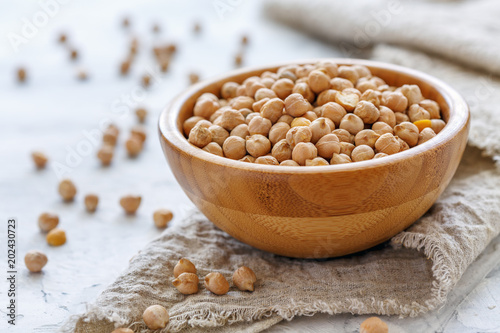 Poster Graine, aromate Chickpeas in wooden bowl on a linen cloth.