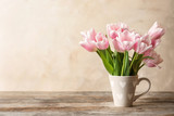 Fototapeta Tulipany - Cup with beautiful tulips for Mother's Day on table