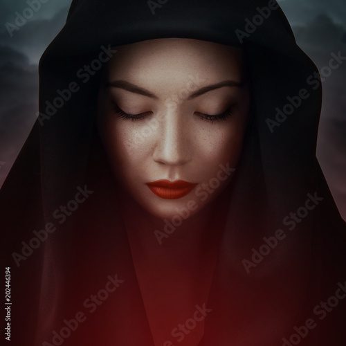 4cd560d1ef4 Beautiful woman big eyes covers her face with a black cloth. Red lips girl  under hood. In colorful bright lights