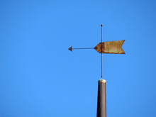 Old Rusty Weather Vane Against Clear Blue Sky. Vintage Windvane On Top Of The Tower