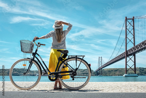 Photo  Blonde woman in summer hat and yellow skirt with her city bicycl