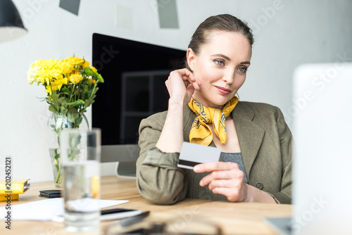 Fotografie, Obraz  smiling stylish businesswoman holding credit card and looking at laptop in offic